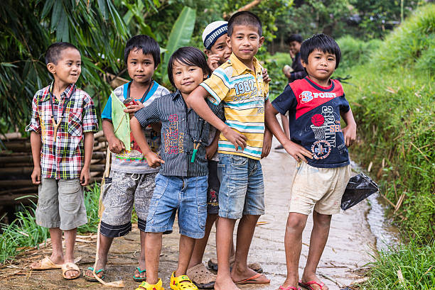 Children playing with the photographer Mamasa, Indonesia - August 17, 2014: Group of unidentified funny children posing, smiling and looking at the camera in the countryside of Mamasa, Sulawesi, Indonesia. indonesian ethnicity stock pictures, royalty-free photos & images