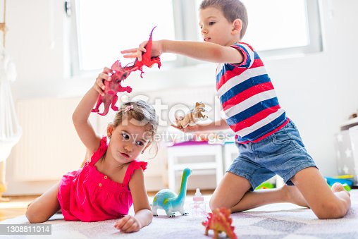 Children playing with toy dinosaurs in their room.
