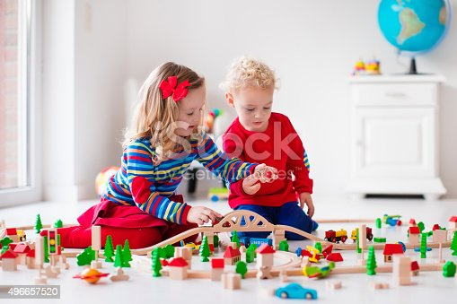 istock Children playing with toy railroad and train 496657520