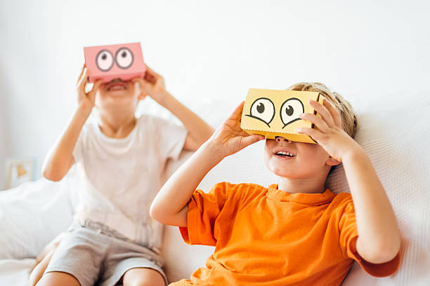 Children playing with Virtual Reality Headsets Two kids playing with VR Headsets with Comic eyes drawn on them. The VR sets have been customized by the Photographer. cartoon and kids stock pictures, royalty-free photos & images