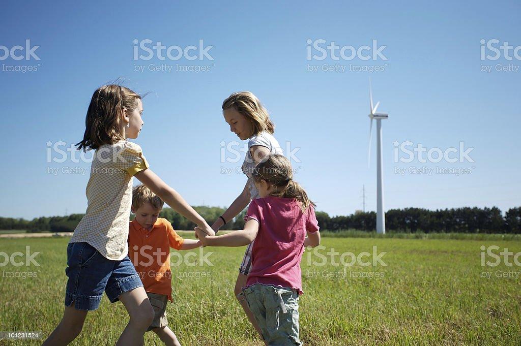 Enfants jouant avec éolienne en arrière-plan - Photo