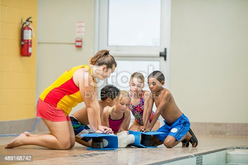 A multi-ethnic group of elementary age children are at a swimming lesson in a gym next to the pool, they are learning about CPR and are taking turns practicing with the help of a lifeguard.