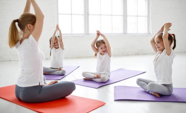 Kinder üben dabei, Gymnastik und Yoga mit Lehrer – Foto