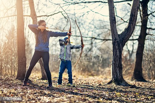 istock Children practicing shooting bows in forest 1130440352