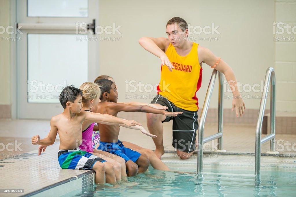 Children Practicing Swim Strokes stock photo
