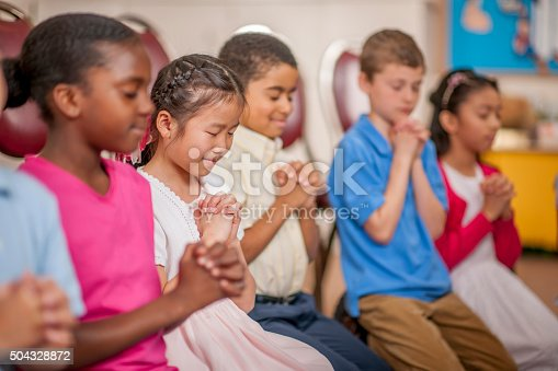 A multi-ethnic group of elementary age children are kneeling on the floor and are praying together.
