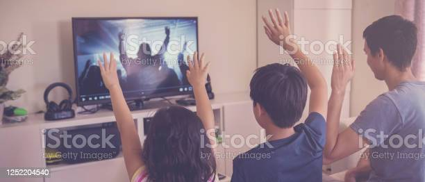 Photo of Children praying with father parent , family and kids worship online together at home, streaming church service, social distancing concept