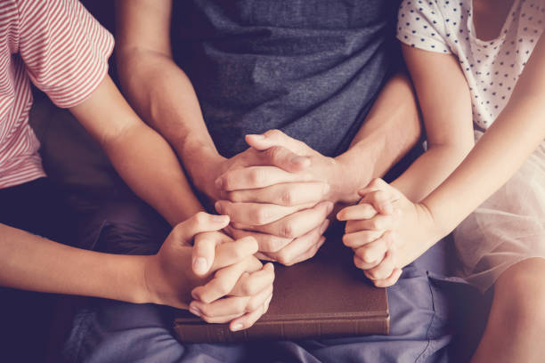 children praying with their parent at home, family pray, Having faith and hope. stock photo