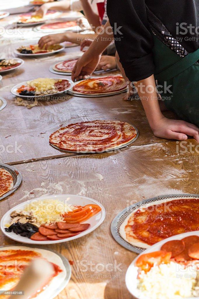 children prepare the pizza in the kitchen stock photo