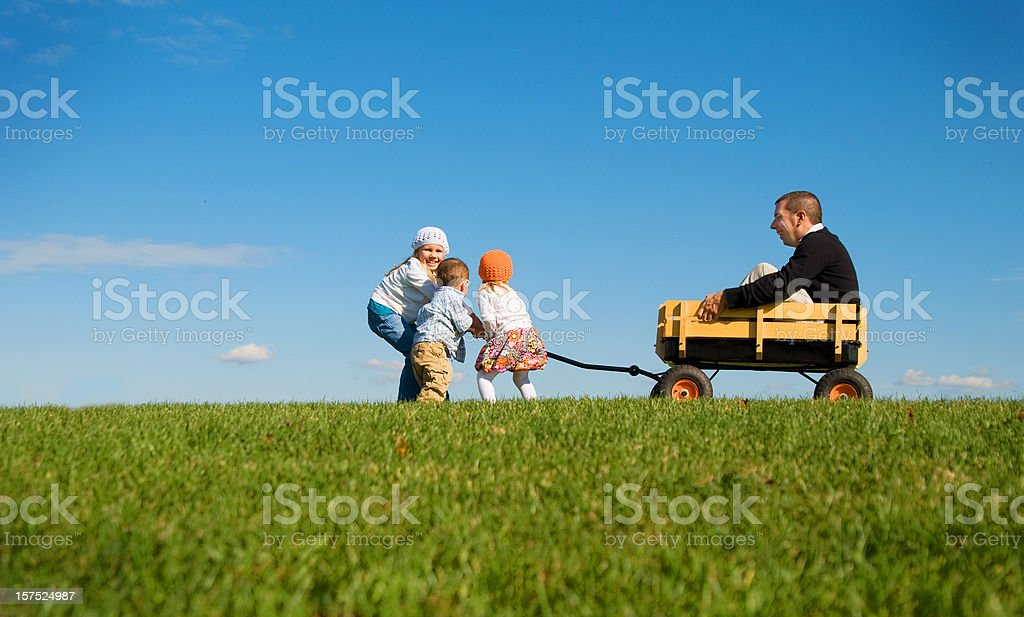 Children pulling Daddy in Wagon royalty-free stock photo