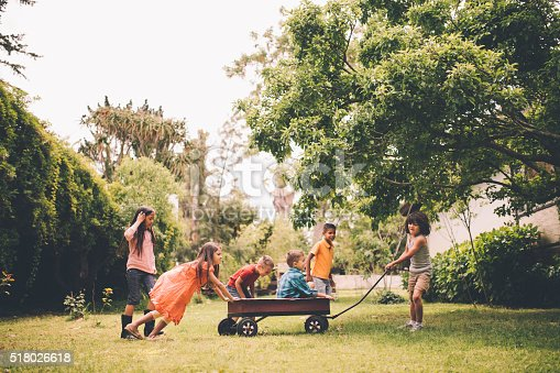 Group of children playing in a park together with some sitting in a red wagon with other friends pushing and pulling