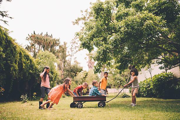 Enfants fond et en ramenant vos amis en Rouge chariot dans le parc - Photo