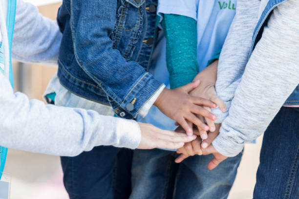 children put their hands together in unity - take care of your jeans imagens e fotografias de stock