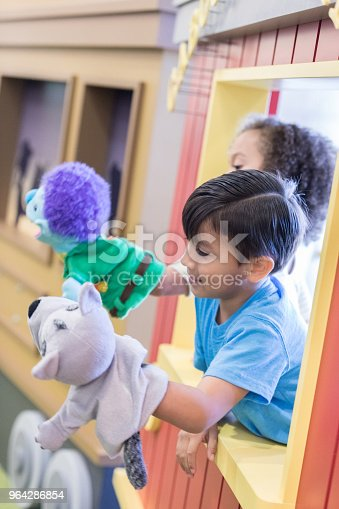 Young children put on a puppet show for their family and friends.