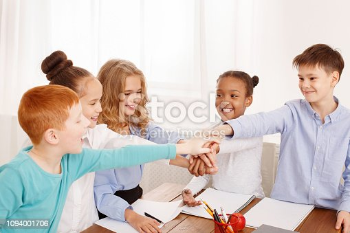 866758230 istock photo Children putting their hands together in classroom 1094001706