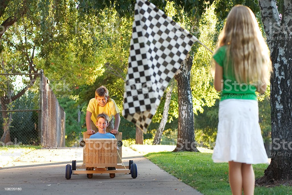 Children Racing in Push Go-Cart on Sunny Day royalty-free stock photo