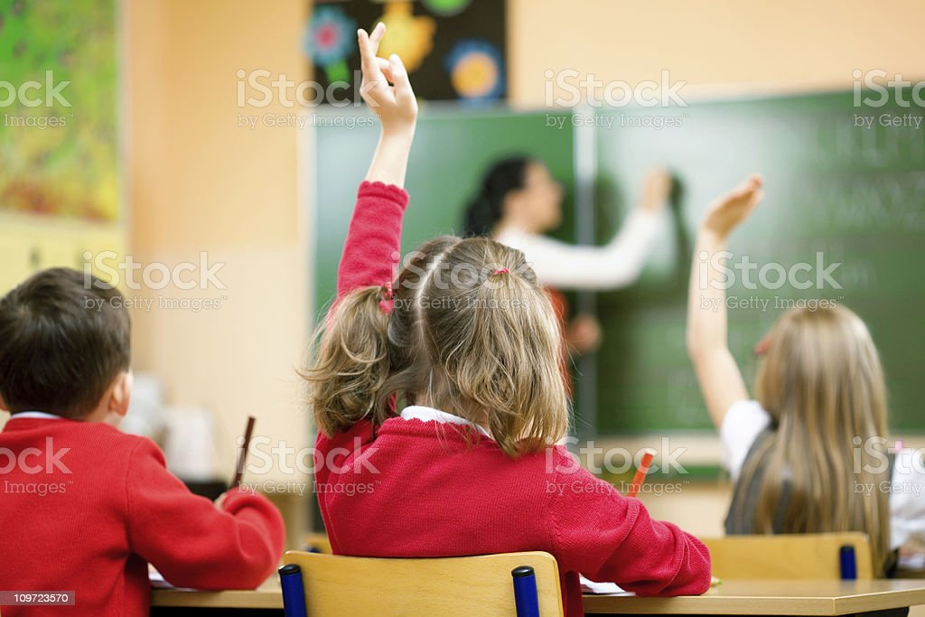 Children Raising Hands In Class, Rear View royalty-free stock photo