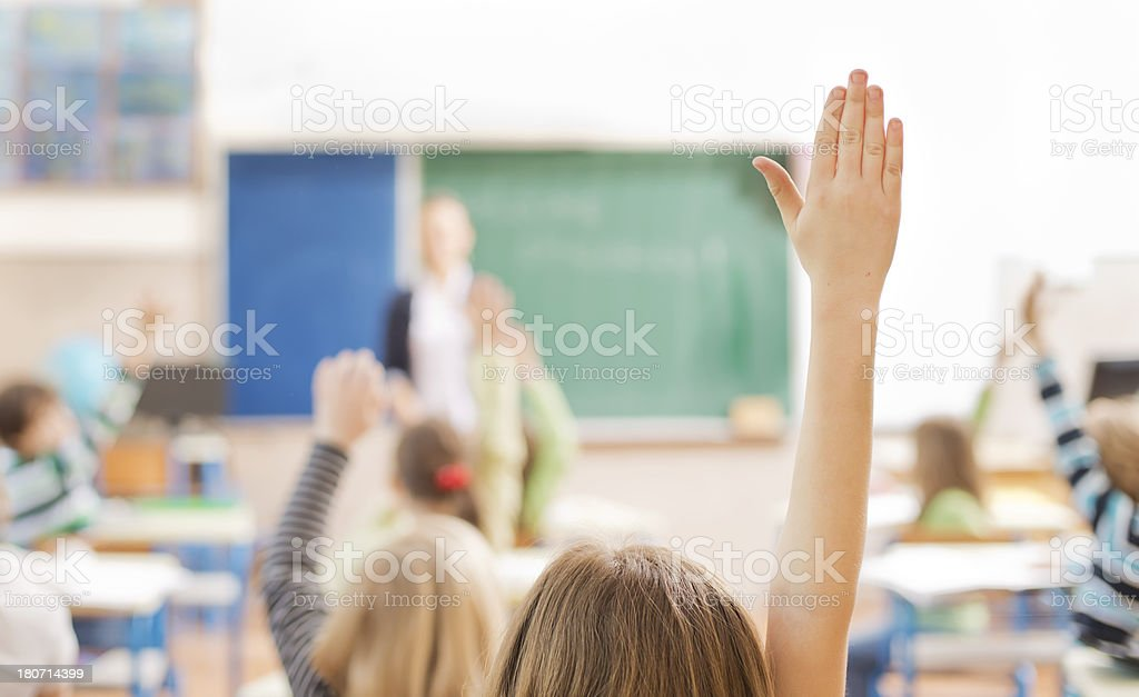 Children raising their hands in the classroom stock photo