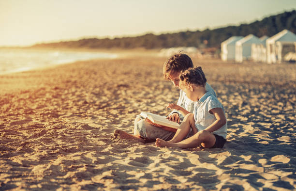 Children reading a book on beach at sunset stock photo