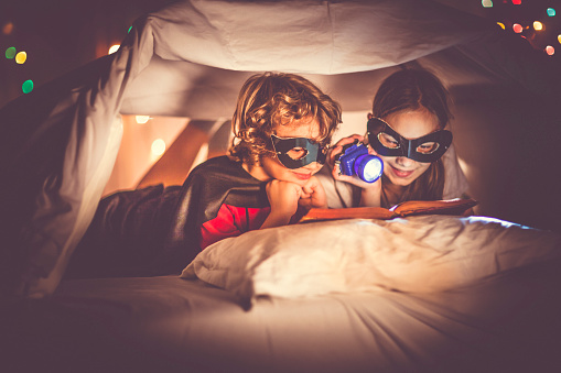 Two children are reading a book in bed under a sheet.  Little boy is wearing a superhero costume. They are hiding under a homemade playing tent, made of bedding. Next to him, the little girl is reading a story book with a flashlight in her hand.