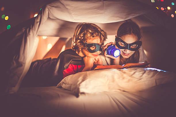 children reading a book past their bedtime - geschichten für kinder stock-fotos und bilder
