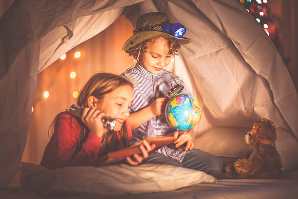 Children reading a book past their bedtime – Foto