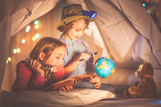 Children reading a book past their bedtime - foto de stock