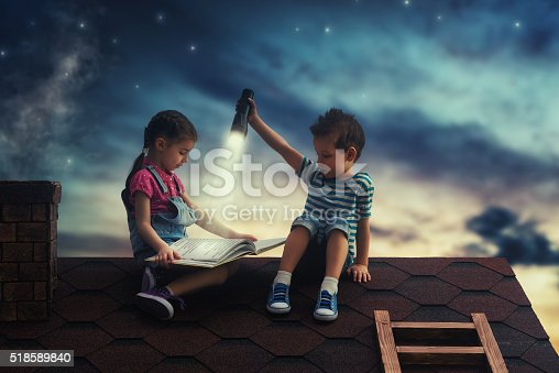 istock Children reading a book 518589840