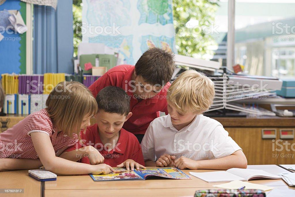 Children reading a comic in school stock photo