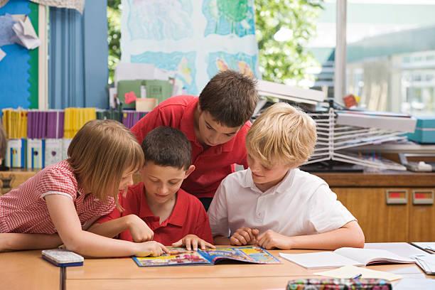 kinder lesen ein comic in der schule - comic stock-fotos und bilder