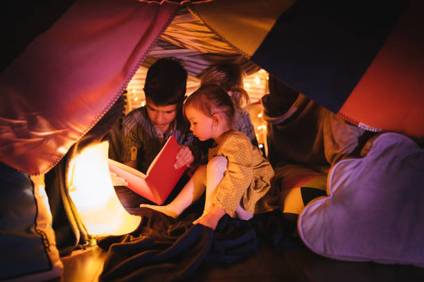 Children reading a story in blanket fort at night stock photo