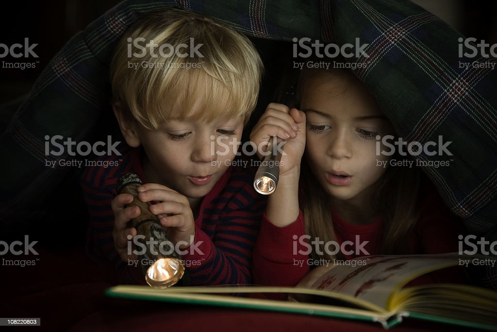 Children Reading Book by Flashlight Under Covers stock photo