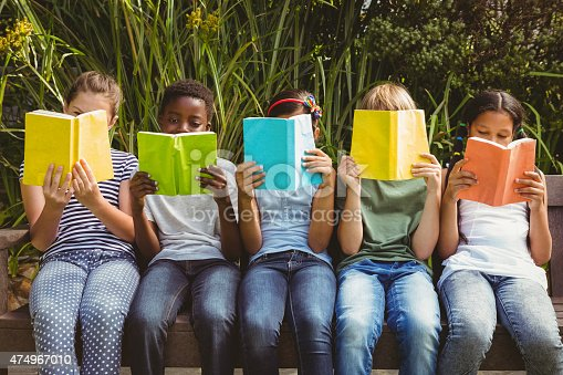 istock Children reading books at park 474967010