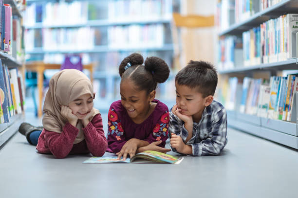 Children Reading Three (3) kids who are friends are laying on the floor in between bookshelves in the library. They are reading a book together. They are all smiling and enjoying their afternoon. elementary age stock pictures, royalty-free photos & images