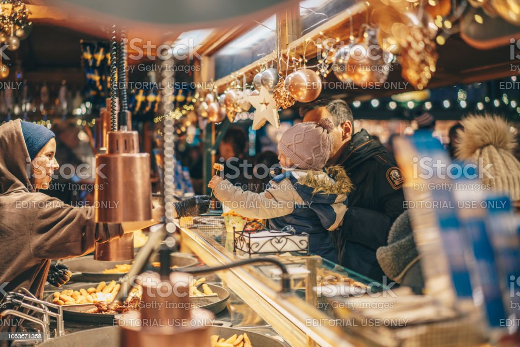 Children receiveing treats the Salzburg Christmas Market at a street food stand stock photo