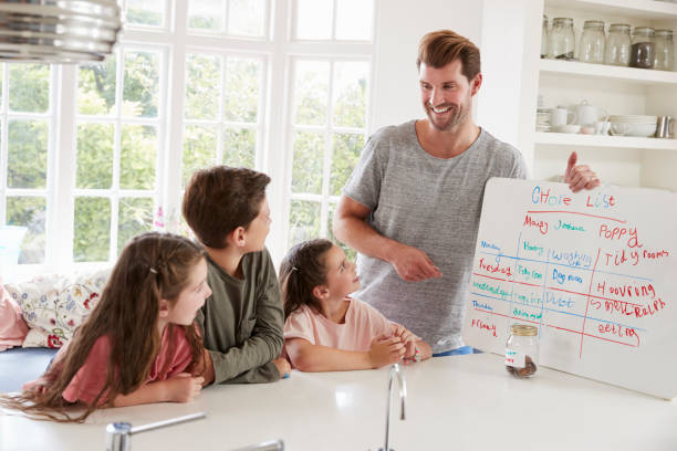 children receiving pocket money after completing list of chores - household chores stock photos and pictures