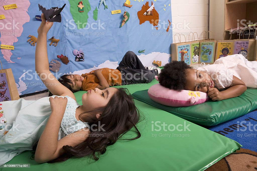 Children (2-5) relaxing in classroom royalty free stockfoto