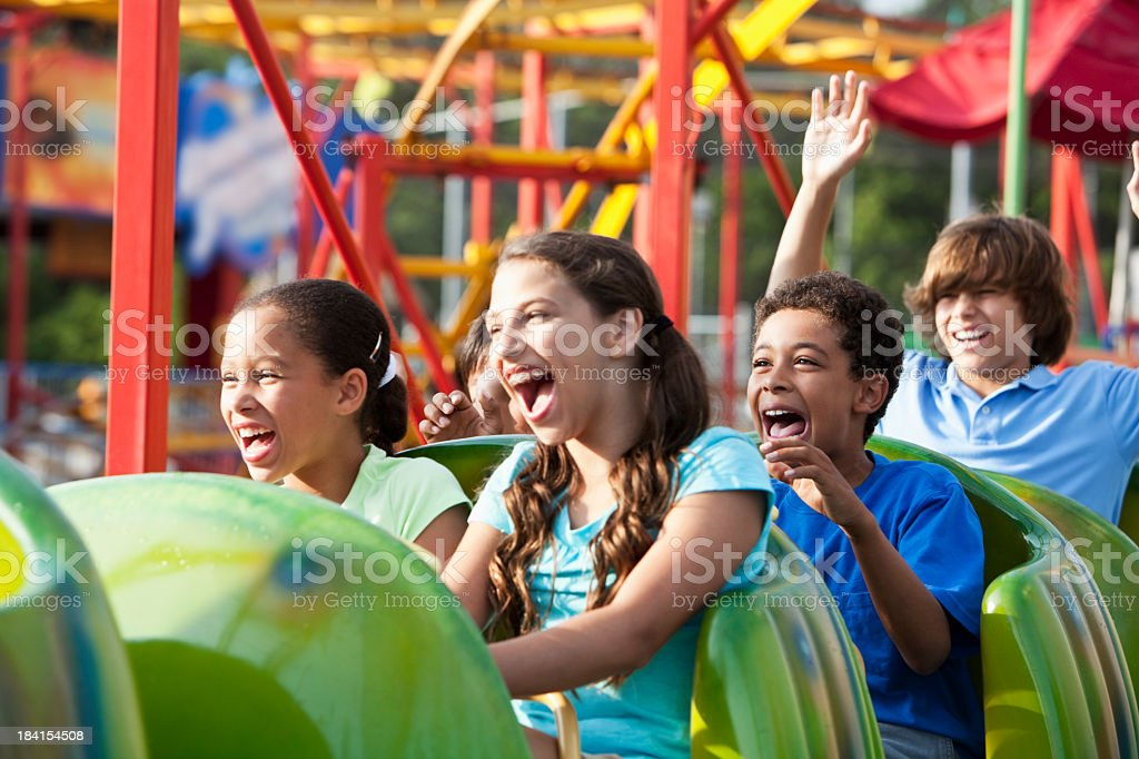 Children riding a roller coaster stock photo