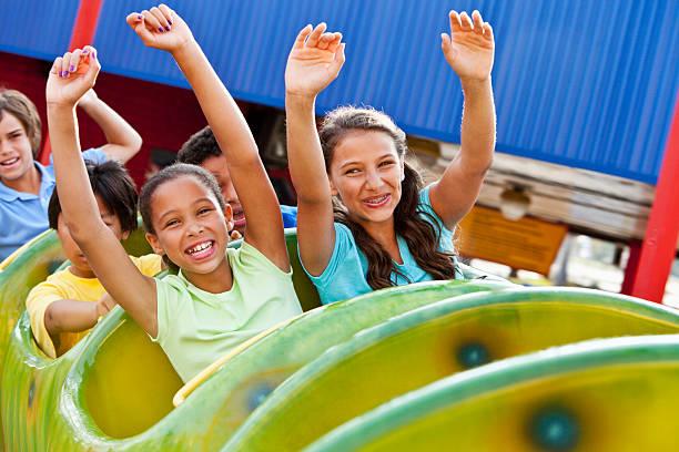 niños montando una montaña rusa - roller coaster fotografías e imágenes de stock