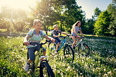 Kids enjoying Spring. They are riding through a field of dandelions.\nNikon D850