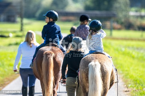 Children accompanied by adults on a horseback riding through park.