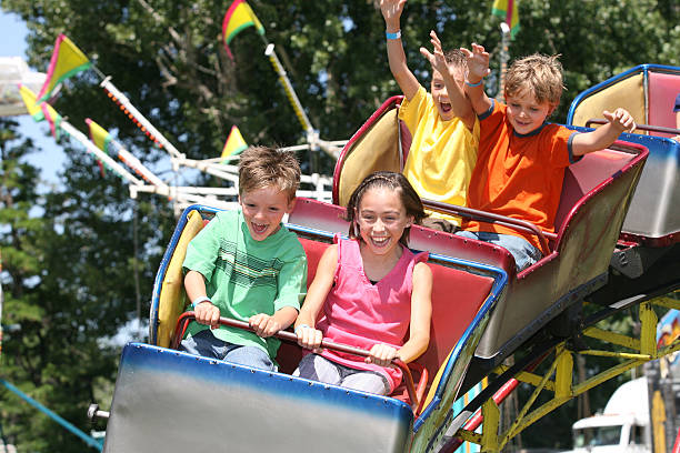 children riding on a roller coaster - roller coaster stock pictures, royalty-free photos & images