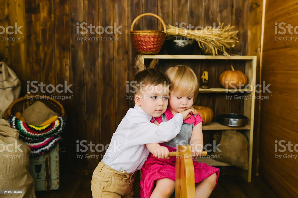 Children riding on a wooden horse stock photo