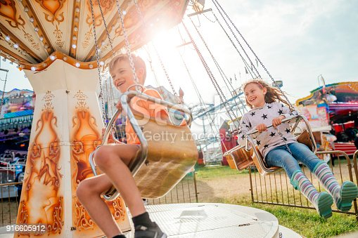 Little girl and boy enjoying riding on the swings while at the fairground