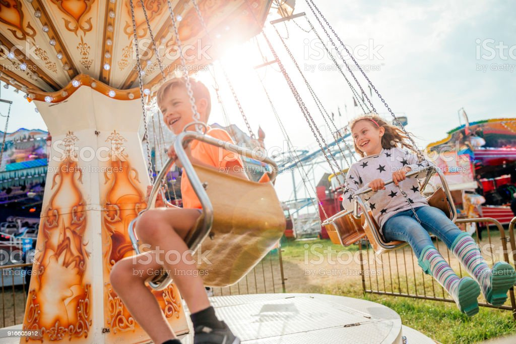 Children Riding on the Swings at the Fairground stock photo