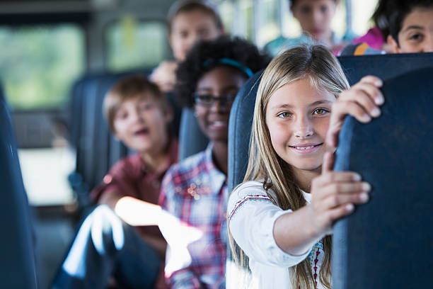 children riding school bus - school bus stock photos and pictures