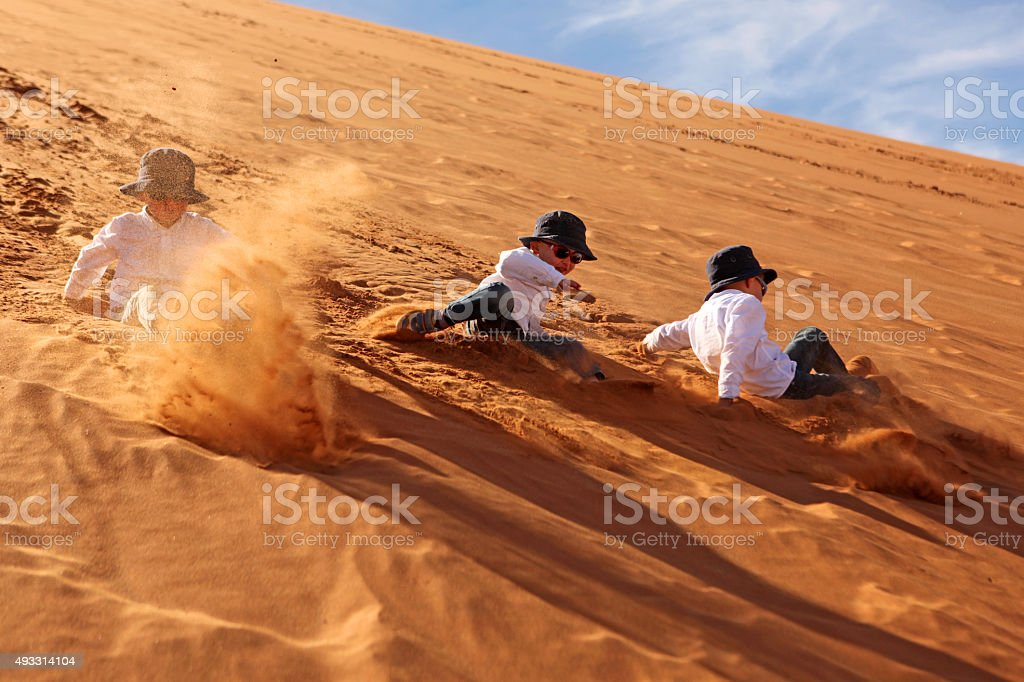 Children Rolling Down the Sand Dunes in Sossusvlei Namibia stock photo