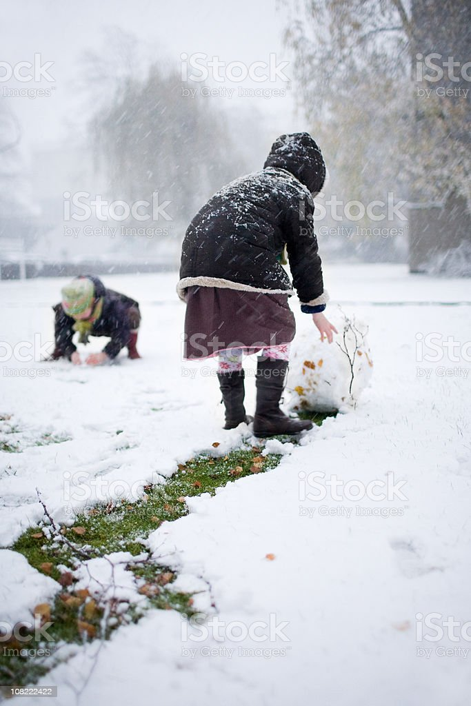 Children Rolling Snowballs for Snowman Outside royalty-free stock photo