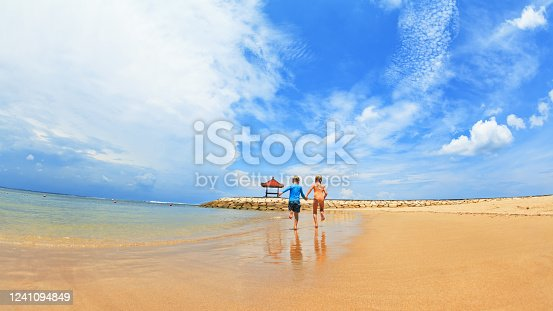 929671306 istock photo Children run with splashes by water pool along sea surf 1241094849