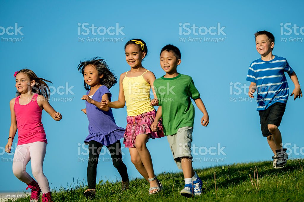 Children Runnign Down Grassy Hill stock photo